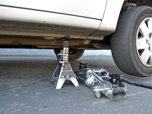 Slowly lower the jack until the jack stand is supporting the car. Remove the jack.