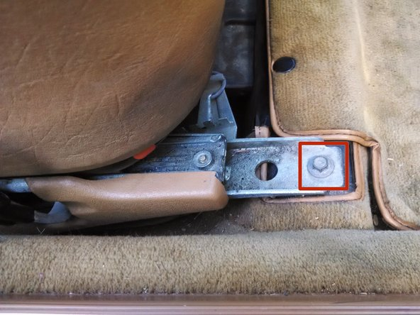 This will similarly expose two 10mm bolts on either side of the front of the seat. Remove these as well.
