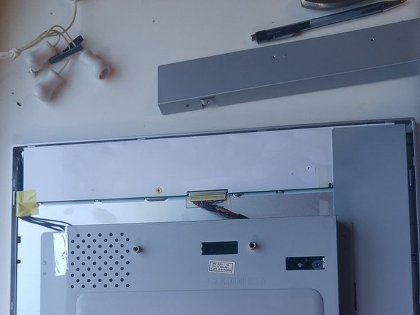 Image 3/3: Remove the tape covering any of the screws or wires we will remove in future steps