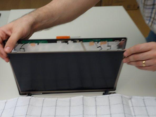 Repérez les deux vis de fixations inférieures de l'écran LCD. Dévissez les.