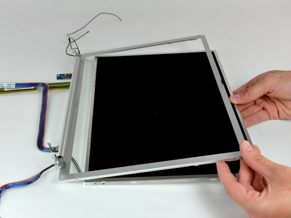 Pull the LCD toward the top edge of the front display bezel, minding any cables that may get caught.