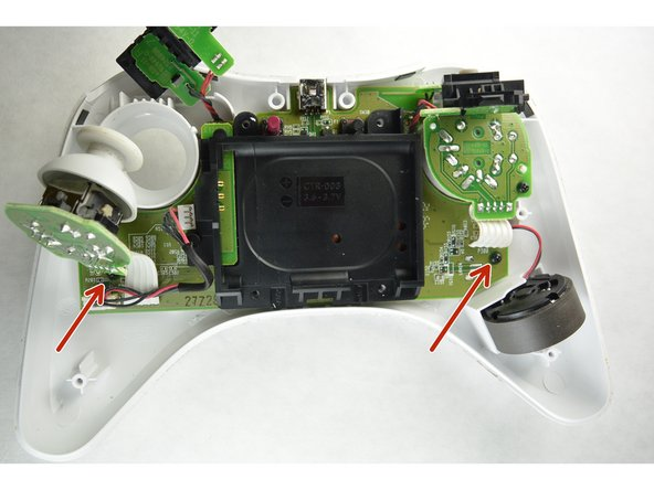 Now that the joysticks are peeled back, one has the ability to take the controller board out of the controller.  Locate the screws on the left and right  hand side of the controller which are highlighted in the photos and use the J0 bit to remove these 4 mm screws.