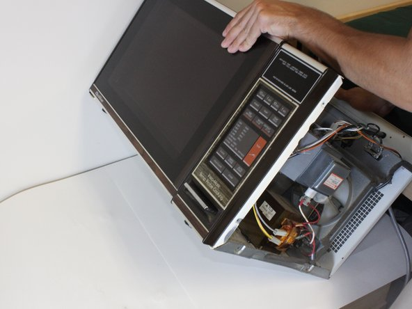 Tip the microwave back so it is lying face up. This allows access to the screws beneath the transformer.