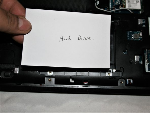 With the screws removed, slide the hard drive away from the center of the laptop and remove it.