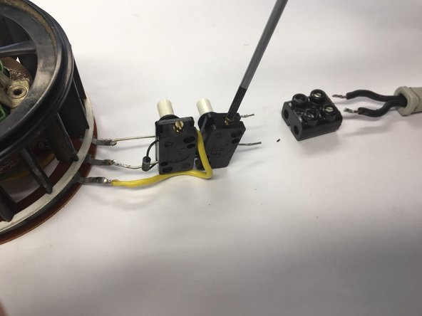 Loosen the flathead screws and remove the wires from the button holder. Remove the button holders. When you unscrew the wire opposite to where the yellow wire is connected, you can slide the button off of the middle wire connected to the motor.