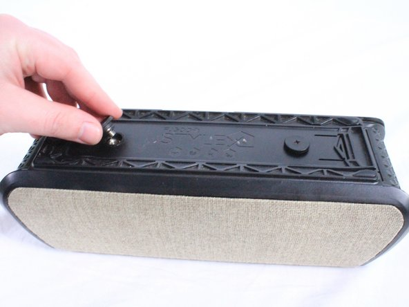 Using your hand, unscrew the large screws underneath the speaker.