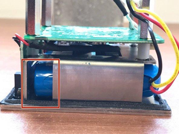 Pousser la batterie de part et d'autre de celle-ci, par l'espace encadré en rouge vers l'extérieur du panier