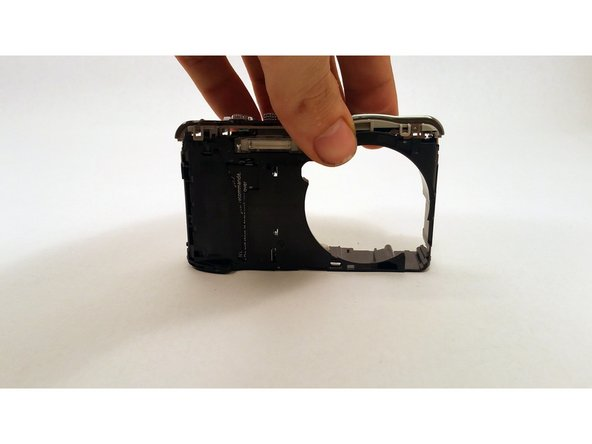 After the front panel is removed, the buttons are connected by a simple string of clips. To remove the buttons, find the clip on the back and the two on the front that are connecting the buttons to the shell of the camera. Remove these clips and pull the buttons up from the back at an angle towards the front to remove them.