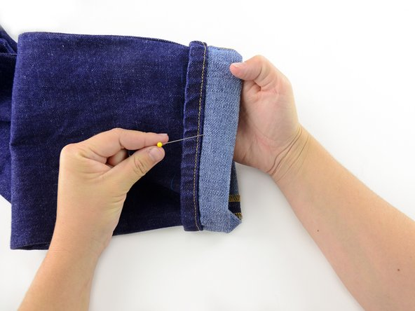 Insert a row of pins perpendicular to the bottom of the cuff, catching the fold and holding it in place.