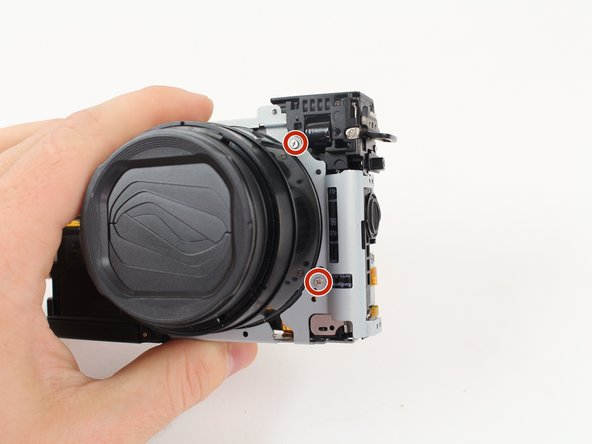 Remove the four 4.25mm Philips screws from the silver frame that surrounds the lens of the camera with a Philips Head screwdriver.