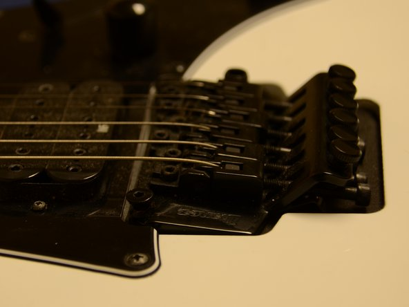 Re-examine the bridge for any changes in bridge balance. If the bridge does not line up with the body of the guitar, move on to the next steps to adjust the tension in the springs on the back of the guitar.