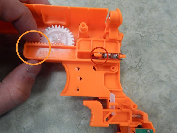 Locate the orange bar protruding from the rest of the gun. You should see the spring hooked onto two ends.