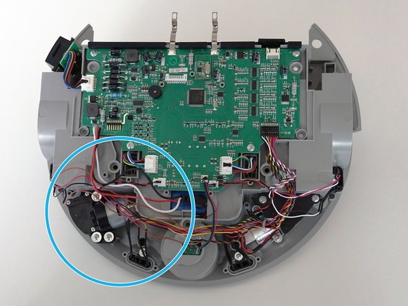 The side brush motor is attached to the right side of the mainboard by one red and black twisted wire.