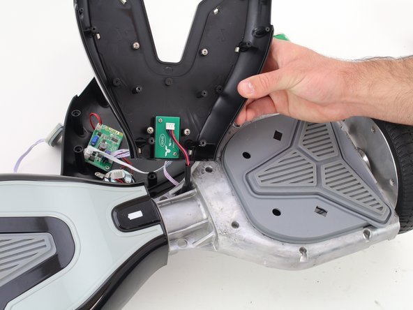 Lift both the left and right sides of the top half of the shell from the hoverboard's chassis.