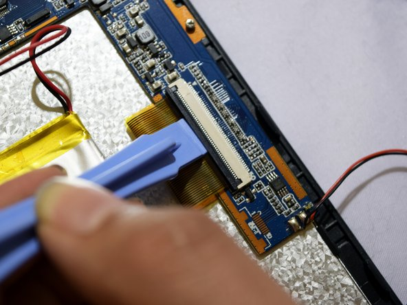 Grip the ribbon located at the far end of the circuit board with a plastic spudger tool.