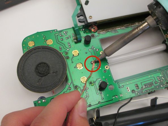 Flip the motherboard back over and desolder the two components that are holding the backlight in place.