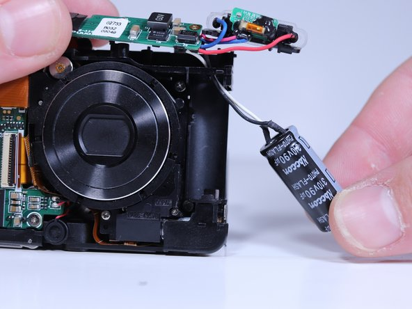 Pull the flash capacitor out of its compartment to expose the wires connected to it.