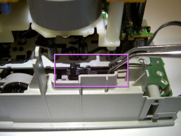 Image 3/3: '''CAUTION:''' When the latch is disengaged, the tape cover may push out and force the rest of the apparatus to pop up. This is normal, but be careful that the tape cover does not pop out too quickly.