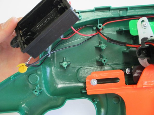 Lift the battery box off the frame of the gun to give yourself access to the trigger mechanism.