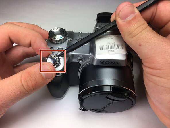 When the new shutter button is laying flat over the hole, twist it counterclockwise to lock the button in.