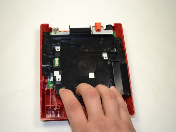 Using your fingers, pull the black plastic tray toward you to loosen it from the console.