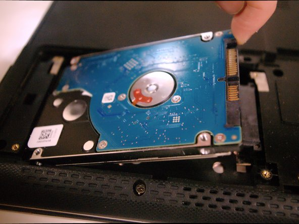 Gently slide the hard drive left toward the edge of the laptop, then lift up to remove it.