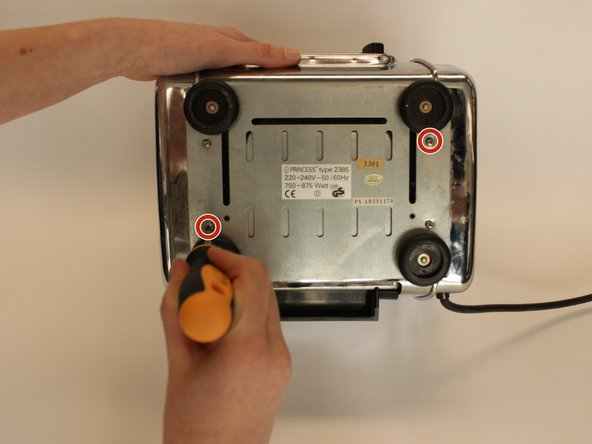Use a crosshead PZ #1 screwdriver to unscrew the bottom left and top right 5 mm crosshead screws.