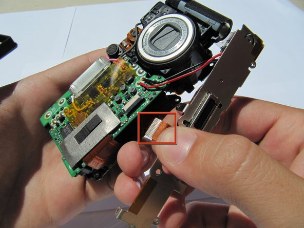 Image 1/1: Carefully disconnect the orange flex cable.