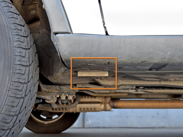 Image 2/2: The stand point is below the rocker panel on the driver's side of the car, just behind the front wheel