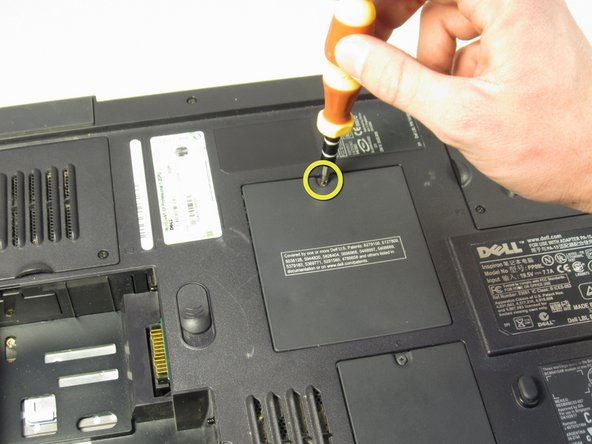 "Using the Philips #00 screwdriver, undo the screw on the memory module cover, labeled ""M."""