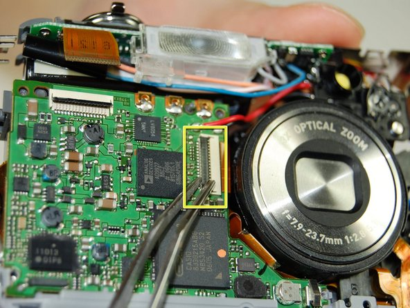 On the logic board next to the lens is a connector with a ribbon.