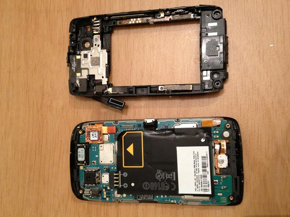 Image 2/2: Gently pry ribbon cable off, and then you will have the back cover fully removed