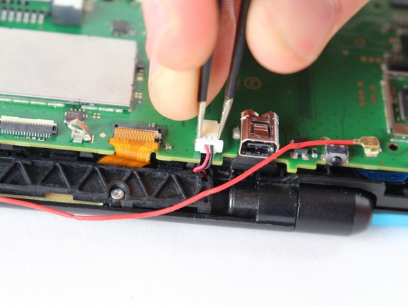 Using tweezers, gently pull out the plug located next to the charging port.
