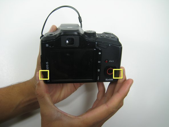 Apply pressure on the left and right side of the camera and pull the back cover away from the device.