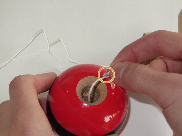 Thread the free end of the string through a small plastic bead, and allow the bead to slide down into the ball.