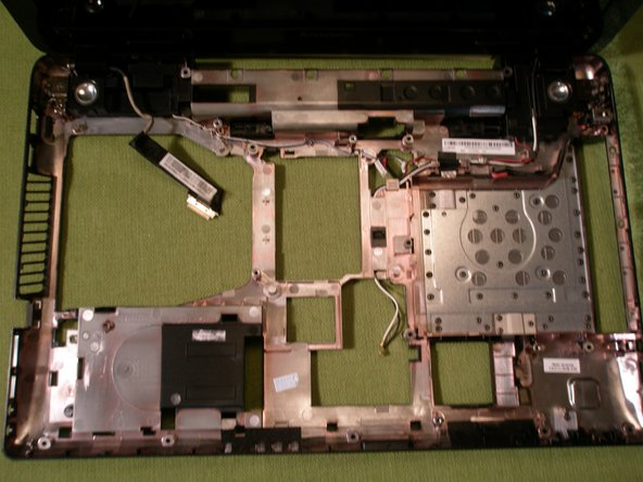 Loosen the screw on the left LCD hinge and carefully lift the Motherboard from the chassis.