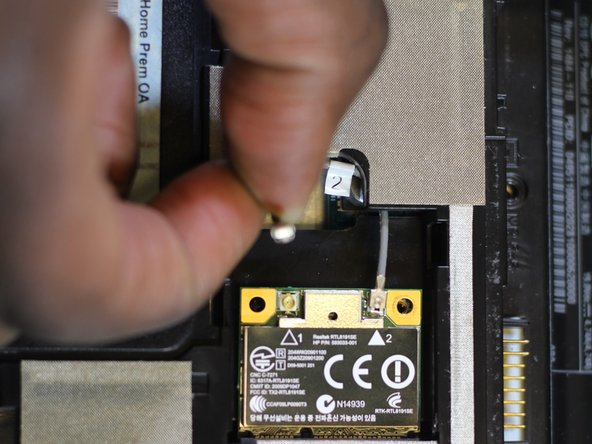 Using your hands, gently remove the cables connected to the wireless card.