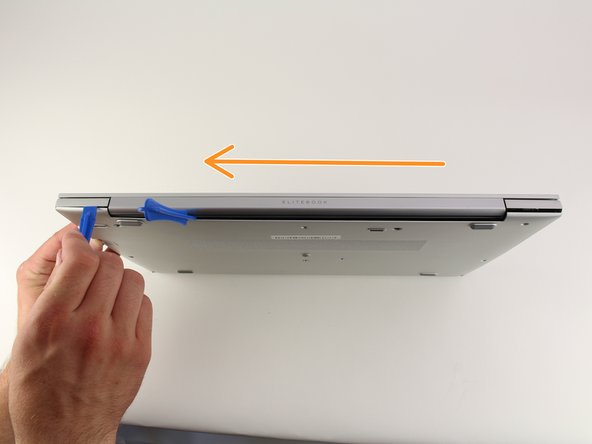Drag the plastic opening tool along the edge from left to right and use a second opening tool to pry open the top right corner.