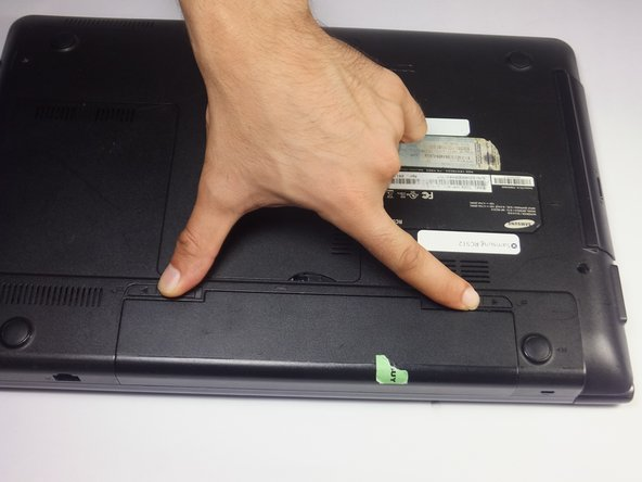 Image 1/2: Slide both battery locking notches to either side to remove the battery.