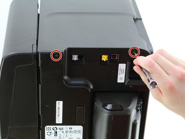 Remove the two 12mm T10 Torx screws on the top edge of the printer.