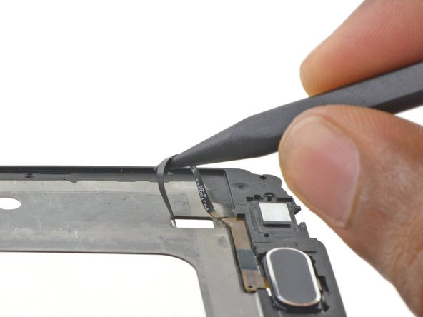 Flip the display frame over and use the pointed end of a spudger to pull the home button cable completely through the hole.
