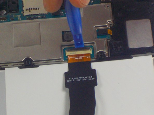 Gently remove tape over ribbon cable connectors and set it to the side. Using the opening tools, gently lift the connector latches to disconnect the ribbon cables.