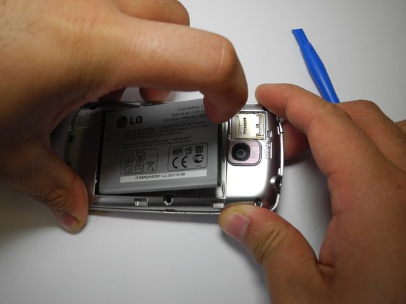 Remove the battery. There's an indentation to the left of the camera lens.