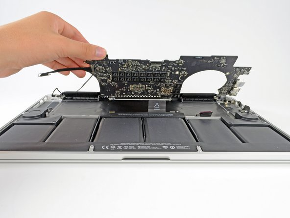 Image 1/2: Using the flat end of a spudger, carefully push the MagSafe 2 connector out of its socket on the bottom of the logic board.