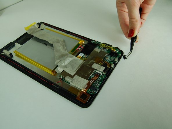 Using tweezers, gently grab the power button and pull it out from the tablet.