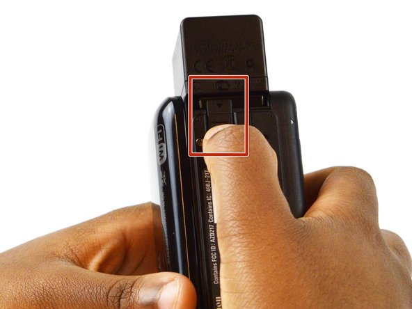 Image 1/1: Hold the battery into place and gently push down on the latch towards the lens.