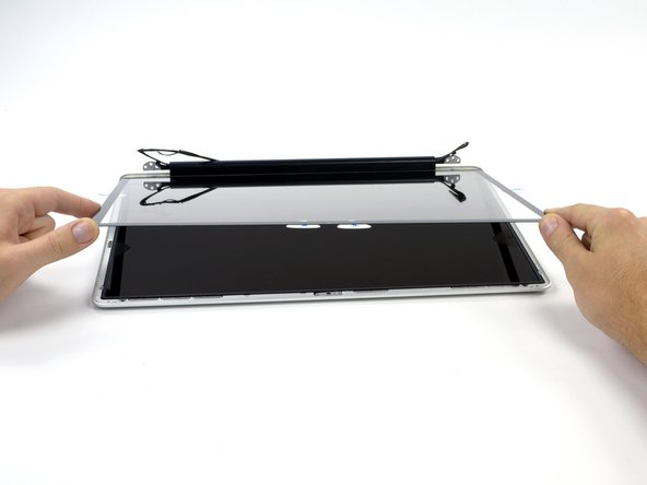 Image 2/3: Slowly lift the top edge of the glass panel and gently rotate it out of the display.