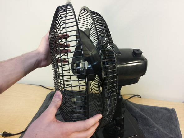 Image 3/3: Once the front end of the cage is free, remove it from the fan and place it to the side for now.
