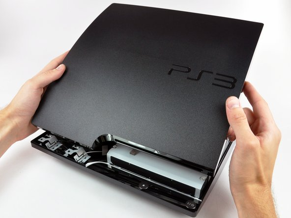 Image 2/2: Lift the top cover off the PS3.