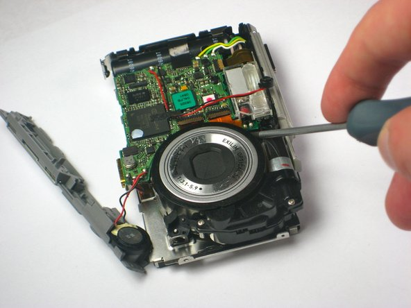 The lens is held in place by two metal tabs: one located directly under the circuit board between the flash and the lens and the other located between the lens and the speaker.